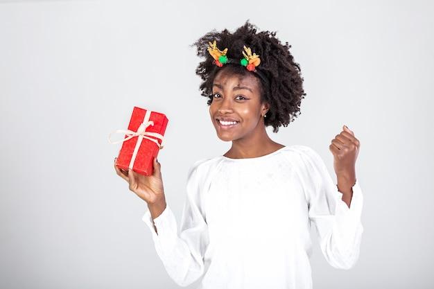 プレゼントを持っている彼女の頭にトナカイの角を持つ若い美しい黒人女性。プレゼントを持った女性。贈り物と幸せな女の子。
