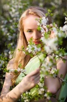 咲く桜の木に立っていると花を見て黄色のドレスの若い美しい金髪笑顔の女性
