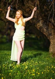 咲く桜の上に芝生の上をジャンプ黄色の透明な布で若い美しい金髪笑顔の女性