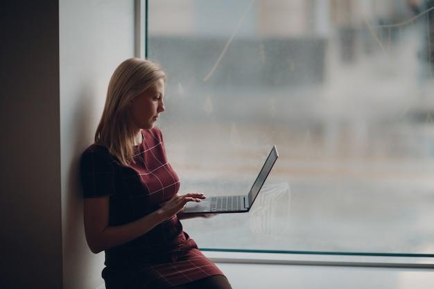 Молодая красивая белокурая девушка студента при компьтер-книжка сидя на большом окне