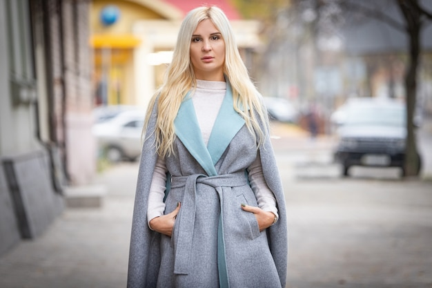 Young beautiful blond woman in an autumn coat stands on a city street. soft focus. fashionable concept.