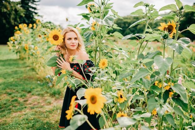 Young beautiful blond woman in black dress in sunflower field