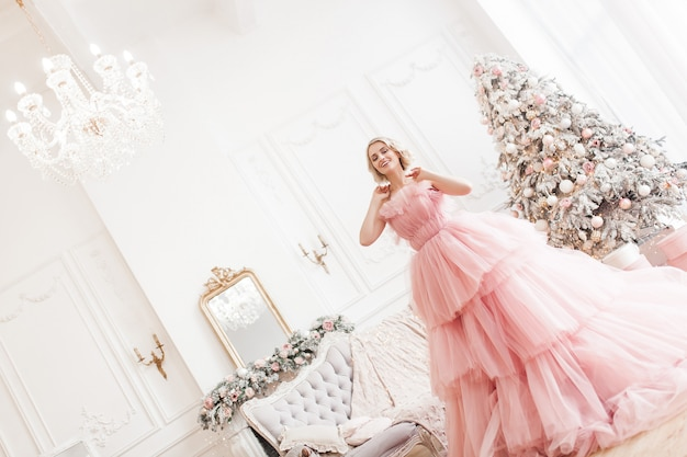Young beautiful blond woman on christmas scene full height. attractive lady in pink gorgeous dress.
