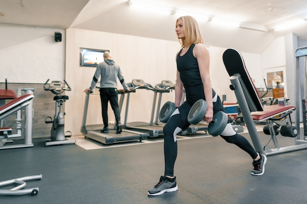 Young beautiful blond woman doing strength exercises