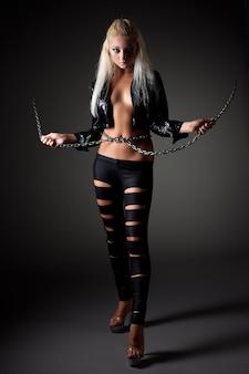 黒いセクシーな衣装を着た若い美しいブロンドの女性が立って、黒いスペースの上に手で巨大なチェーンを保持しています