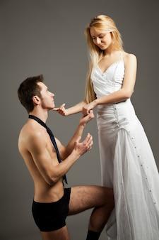 서서 속옷에 남자를 만지고 무릎에 서 넥타이 웨딩 드레스에 젊은 아름 다운 금발 여자