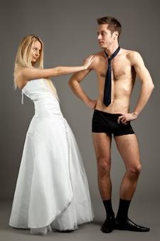 Молодая красивая блондинка женщина в свадебном платье стоит и трогает мужчину в нижнем белье и галстуке, стоя на коленях