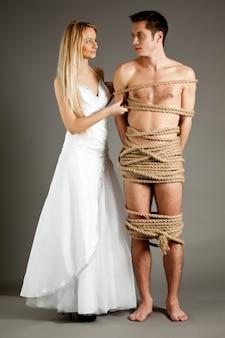 Молодая красивая блондинка в свадебном платье стоит рядом со своим обнаженным мужчиной, связанным веревками на сером фоне