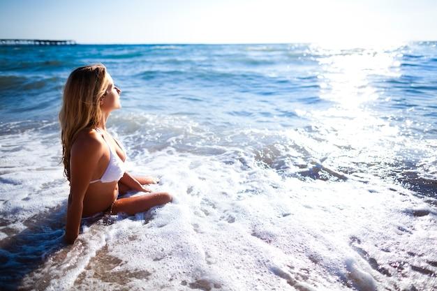 Молодая красивая блондинка женщина в белом бикини, сидя на краю морской воды