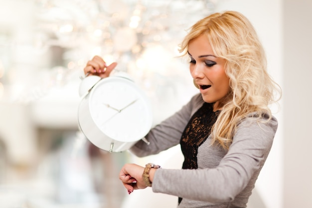 Young beautiful blond woman looking at alarm clock and watch and feeling in hurry