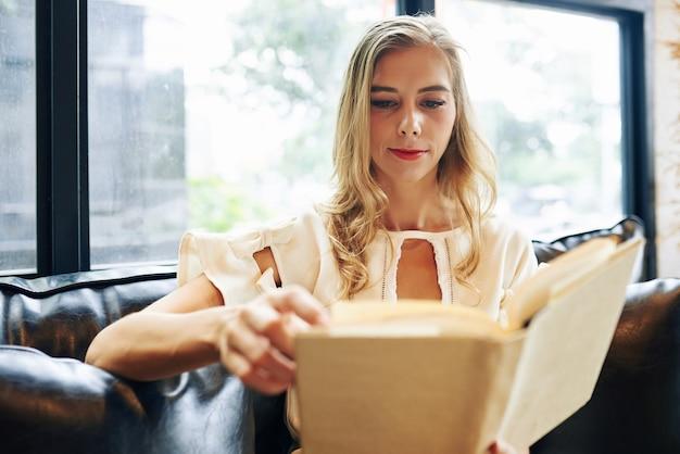 Young beautiful blond woman reading interesting novel