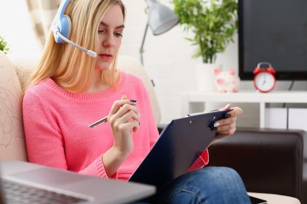 Молодая красивая белокурая женщина сидит на диване в гостиной, держа переплет в руках, работает с ноутбуком, слушает музыку