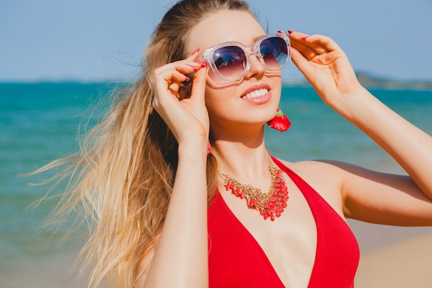 Young beautiful blond woman sunbathing on beach in red swimming suit, sunglasses