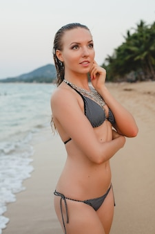 Young beautiful blond woman sunbathing on sand beach in bikini swimming suit, vintage necklace