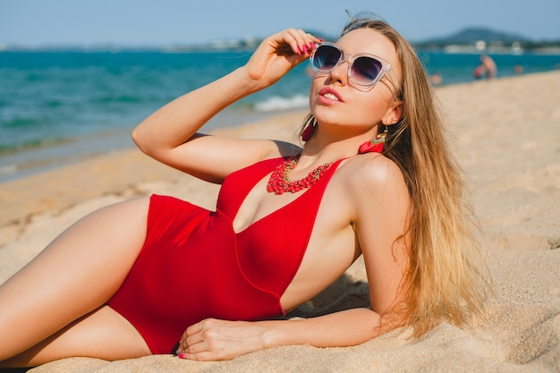 Young beautiful blond woman sunbathing on sand beach in red swimming suit, sunglasses