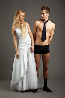 Young beautiful blond woman in wedding dress standing and holding man in underwear by tie and looking at him over grey background