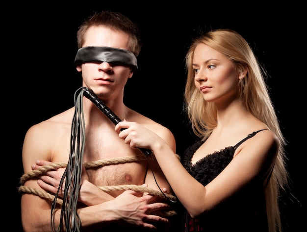 Young beautiful blond woman in wedding dress standing near her naked man tied up with ropes and holding leather lash in hand over greyspace