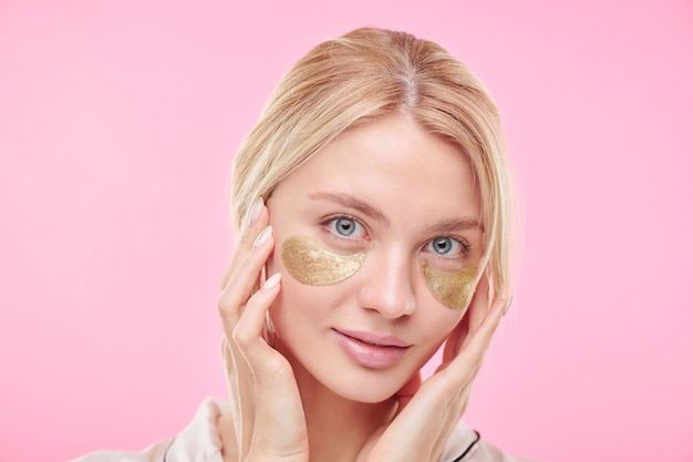 Young beautiful blond woman with golden revitalising under-eye patches keeping hands on her radiant face