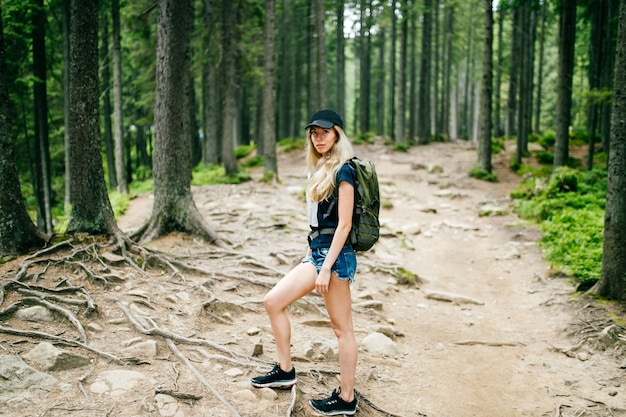 Young beautiful blonde babe portrait. cute lovely female traveler with backpack hiking in mountains at nture on vacation.  tourist woman in camping trip.  walking up the hiils.  skinny stylish girl.