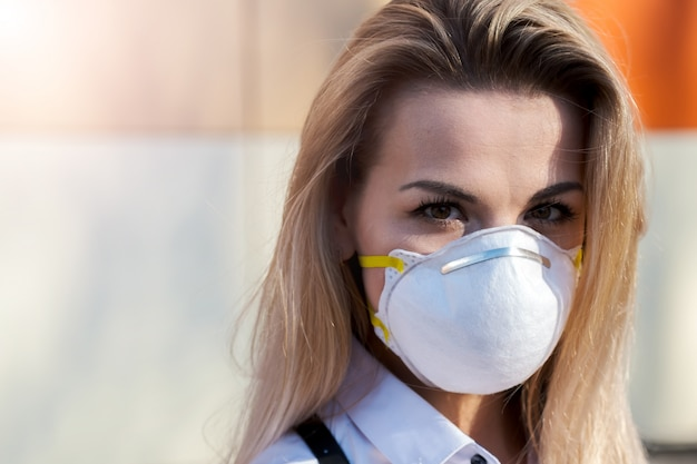 Young beautiful blonde caucasian girl standing in a protective mask outdoors.