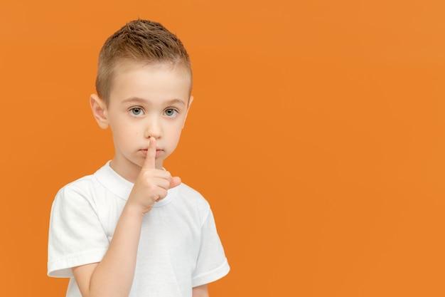 Молодой красивый белокурый кавказский ребенок приложил указательный палец к губам в знак тишины, изолированной на желтом
