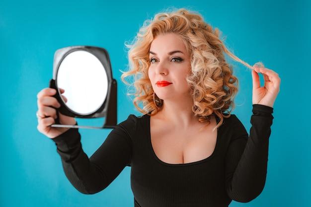 거울을 들고 검은 드레스에 젊은 아름 다운 금발 곱슬 머리 여자