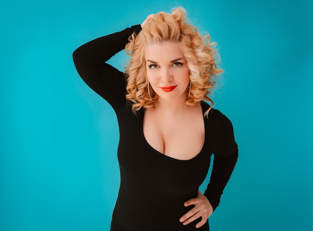 검은 드레스를 입고 포즈를 취하는 젊은 아름 다운 금발 곱슬 머리 여자