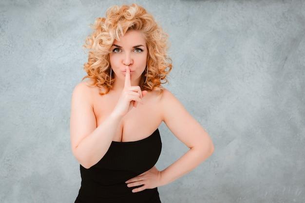 그녀의 입술에 손가락으로 젊은 아름 다운 금발 곱슬 머리 여자