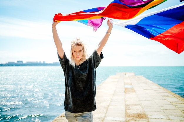若い美しい金髪は、海に向かって虹色の旗とロシアの旗を手に取っている。高品質の写真