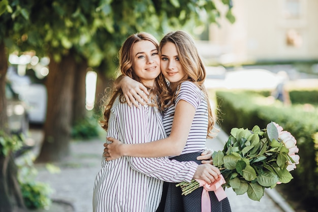 Young beautiful blonde daughter hugs her middle-aged mom on the streets of the city. they are happy and love each other.
