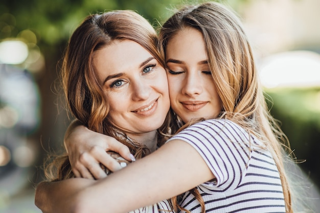 A young beautiful blonde daughter hugs her middle-aged mom on the streets of the city