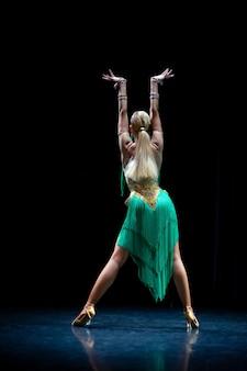 スタジオの黒い背景でポーズをとって若い美しい金髪の女性ダンサー