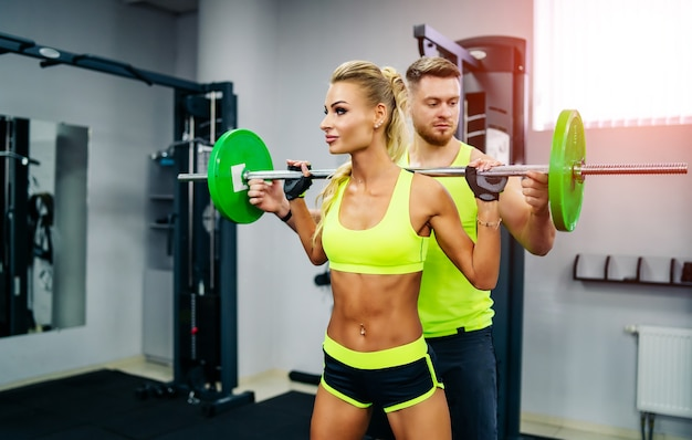 Young beautiful blonde fitness girl trains in a gym on a sport equipment. trainer gives recommendations for better results.