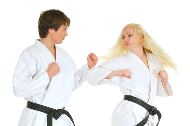 若い美しいブロンドの女の子と着物のスーツを着た若い男空手道が戦っています。空手道と武道の概念。広告スペース