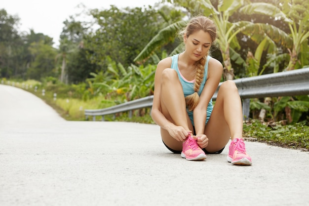 Young beautiful blonde girl athlete in sportswear and pink sneakers tying laces while having break during running workout, sitting on road against green forest  with tropical trees
