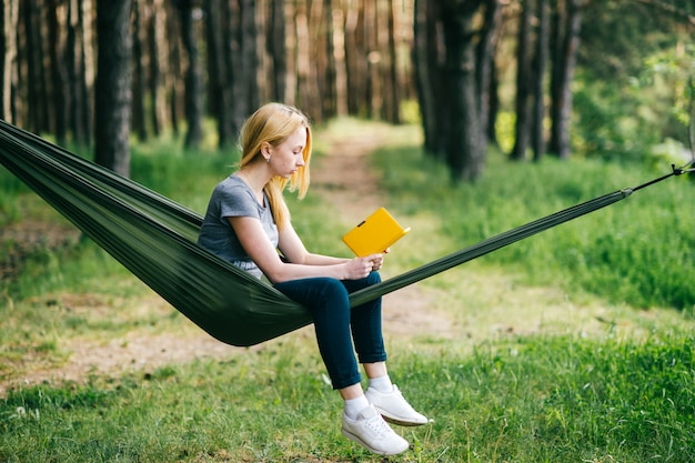 Young beautiful blonde girl in hammock reading e-book in summer forest.