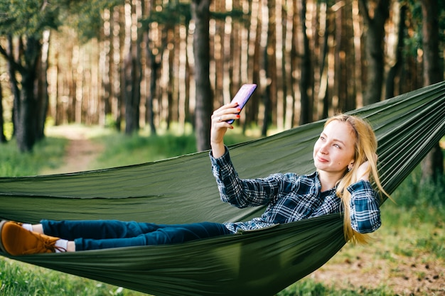 Young beautiful blonde girl in hammock taking selfiein sunny summer forest.