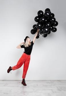흰 벽에 검은 baloons를 들고 젊은 아름 다운 금발 소녀.
