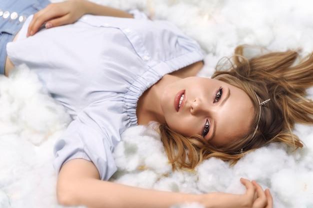 아름 다운 금발 소녀는 구름에 놓여