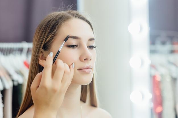 若い美しいブロンドの女の子は鏡の前で自然な化粧をします