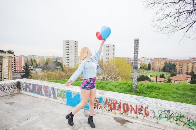 若い美しいブロンドの女の子が風船を弾く