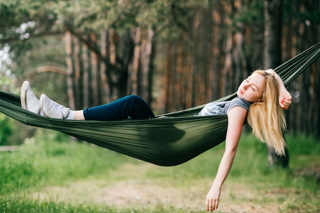 Young beautiful blonde girl relaxing in hammock at nature