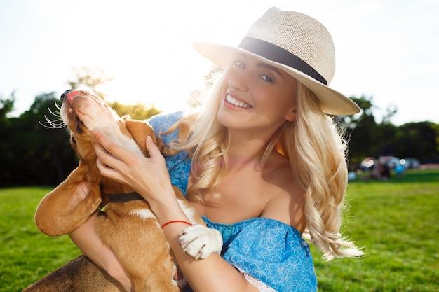 ウォーキング、公園でビーグル犬と遊ぶ若い美しいブロンドの女の子。