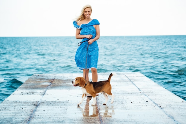 Young beautiful blonde girl walking, playing with beagle dog at seaside.