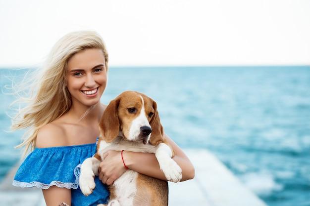 Giovane bella ragazza bionda che cammina, giocando con il cane da lepre in riva al mare.