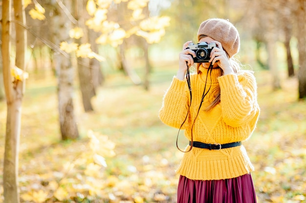 Young beautiful blonde girl with vintage camera have rest in the park in autumn season time.