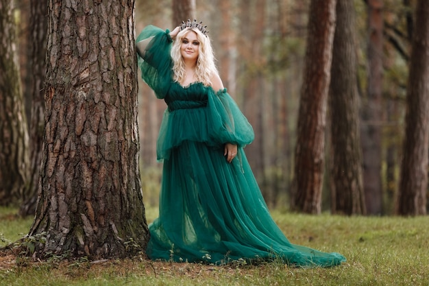 Young beautiful blonde hair woman queen. princess walks. autumn green forest mystic. vintage medieval shiny crown.