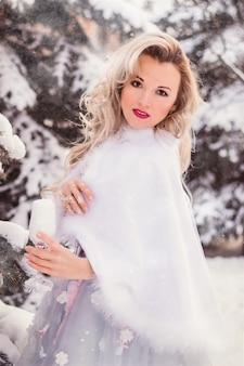 Молодая красивая блондинка в длинном красивом платье в зимнем лесу