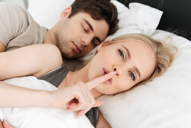 Young beautiful blonde lady showing silence gesture while lying in bed with her man