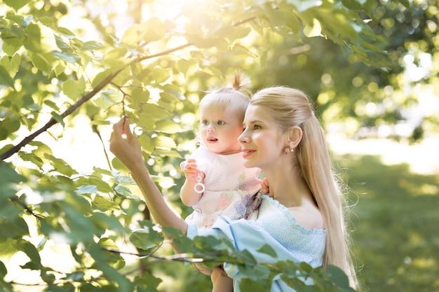 一緒に笑って緑豊かな公園で遊んでいる彼女の女の赤ちゃんと若い美しいブロンドの母親